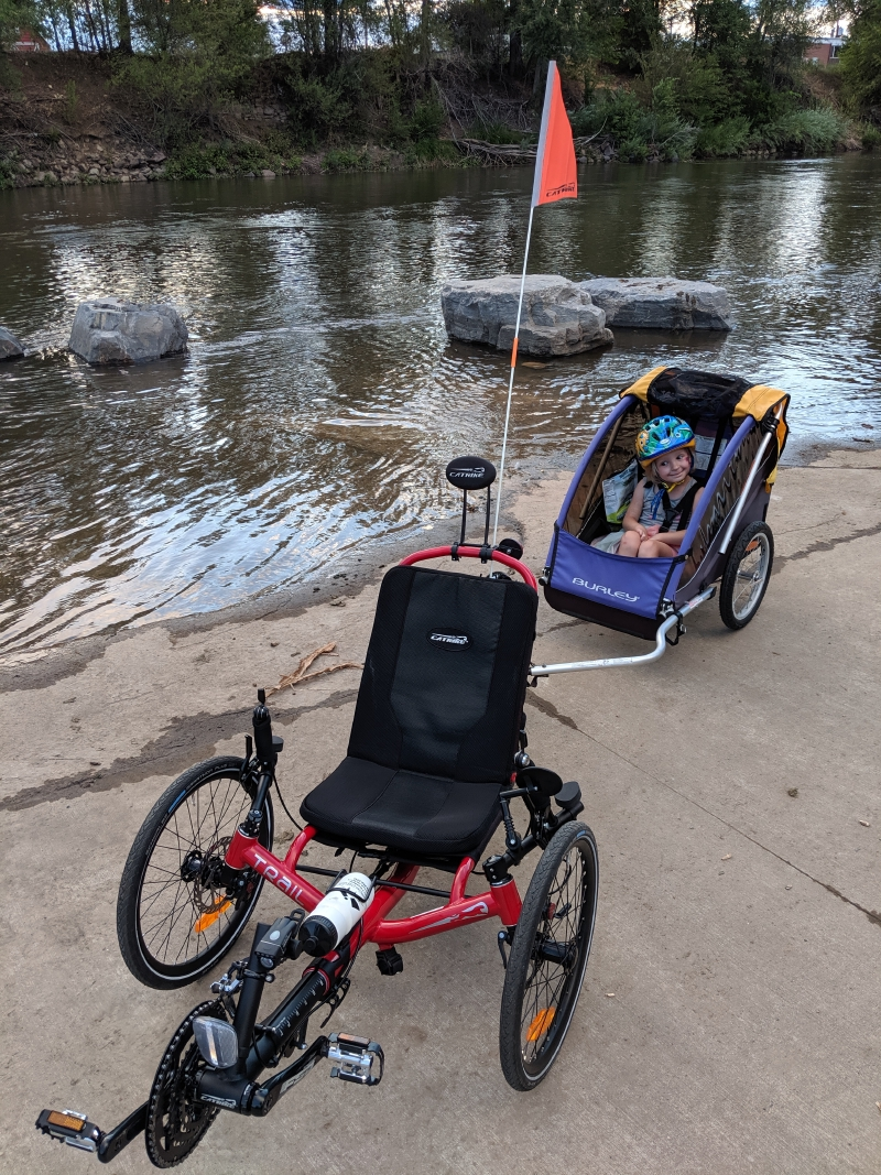 Catrike Trail and hitched trailer (occupied by a smiling kid) parked on the South Platte River bank.